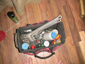A couple of pipe wrenches, various fittings, and a tool bag.