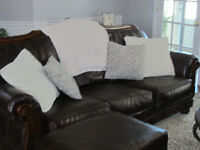 2 Chocolate leather sofas with wood frame & 1 Ottoman