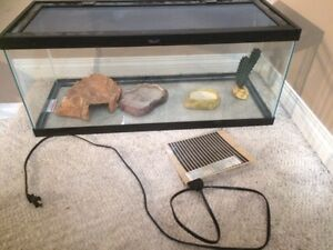 Reptile tank with rock formations and heating pad