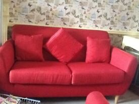 Red three seater and two seater with footstool