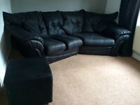 Large curved dark charcoal / black sofa & footstool