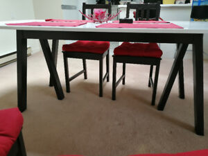 large white oval table with four black and red chairs