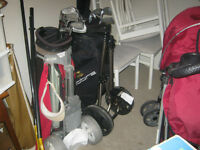 two sets golf clubs with caddys and wheeled holder
