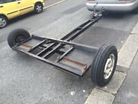 Tow dolly towing a frame recovery single axle trailer