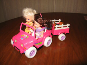 Three Dolls in a toy Jeep and trailer
