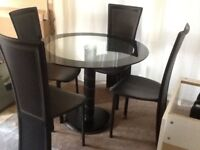 Circular Black and clear glass table & 4 leather effect chairs -Telford