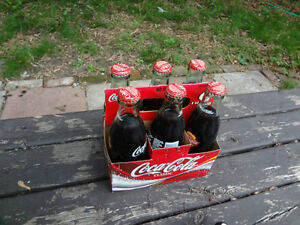Antique Coke Cola bottles with pop in them