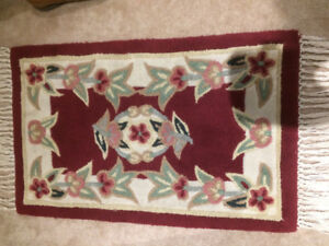 Woollen rug, approx.  40 x21 inches. Red, cream colours, floral.