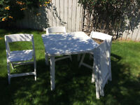 White plastic table and 4 folding chairs