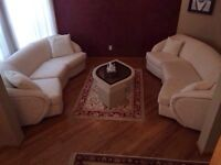 White couches and white stucco coffee table