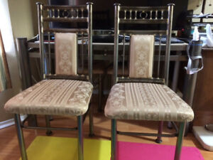 Glass dining room table with 4 matching chairs for sale.