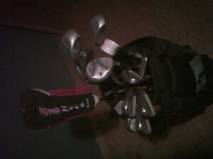 Golf clubs, bag, shoes, and umbrella for sale.