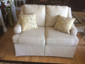 Cushy off white love seat with accent cushions