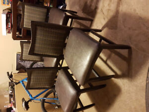 4 matching dark brown kitchen chairs with leather padded seats.