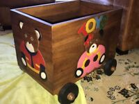 Beautiful hand carved wooden toy box on wheels