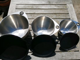 Pampered Chef set of 3 stainless steel bowls with lids.