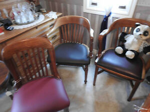 several different antique office  chairs in new leather