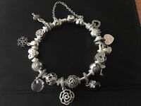Genuine Pandora bracelet with 16 Pandora charms including safety chain.