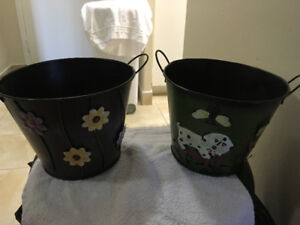 2 black metal planters with handles one with flowers other a dog