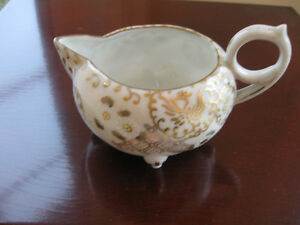 A DECORATIVE OLD HAND-PAINTED ORIENTAL CHINA CREAMER [FOOTED]