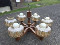 Retro wooden chandelier with tinted glass shades.