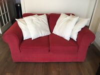 Red 2 seater sofa with 4 cream cushions