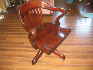 Antique captains desk chair with wheels and leaning spring.