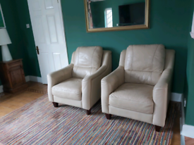 Two cream leather armchairs