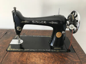 Antique Singer sewing machine in wooden cabinet
