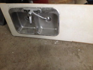 Large double kitchen sink with tap and counter top.