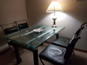 Glass top dining table with 4 black  leather chair