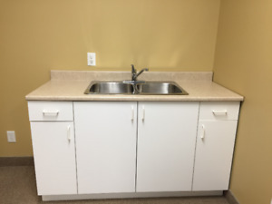 Double sink, cupboard with  Formica countertop