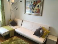 £225.... White faux leather 2 piece clic clac corner sofa -bed. This