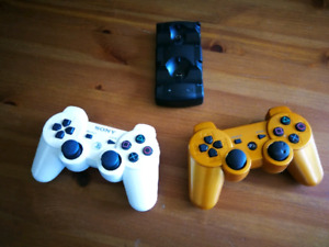 TWO PS3 DUAL SHOCK CONTROLLERS AND CHARGER DOCK