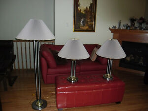 A trio of matching gold and silver metal lamps.