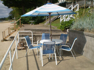Patio table and blue mesh chairs, includes umbrella.