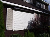 2 Metallic roll down exterior white window storm shutters.