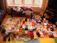 Bags of cloths, a car seat and an exersaucer for sale