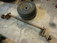 Trailer axle for sale with rims and tires.