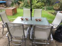 Metal silver six seater glass table and six chairs .