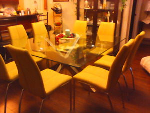 Large glass table with 8 soft green chairs