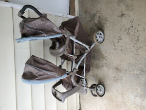 Double stroller with rain cover.
