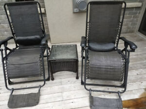 2 gravity chairs and wicker/glass table