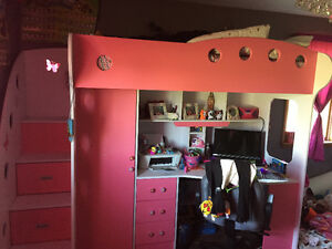 Kids loft bed with, dresser, closet and computer desk.