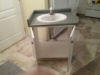 Bathroom cabinet with sink and faucets.