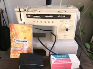 Like new Singer sewing machine with manual cover and xtra pieces