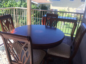 Wooden dining table with 4 cushioned chairs and side table