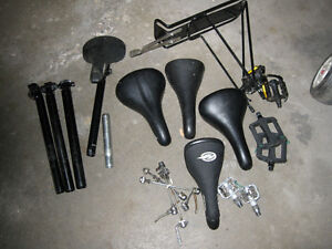 An assortment of bike seats and seat posts and parts