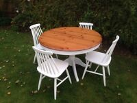 Round extendible dining table and four chairs