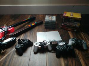 PlayStation 2 Slim with games, controllers, guitars